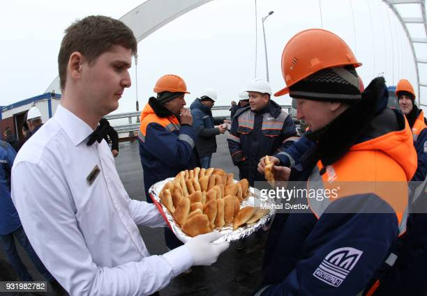A worker takes a cake at the construction site for the Crimean bridge which is being built to connect the Krasnodar region of Russia and Crimean...