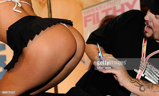 A worker takes a closeup photo of adult film actress Tori Black at the Elegant Angel booth at the 2010 AVN Adult Entertainment Expo at the Sands Expo...