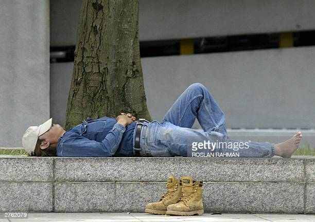 Worker takes a nap during his lunch break in downtown of Singapore 26 November 2003. Singapore's manufacturing output accelerated its growth in...