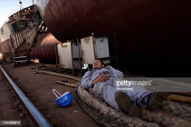 A worker takes a nap next to the Jose de Alencar a Petroleo Brasileiro SA oil tanker under construction at the Maua SA shipyard in Niteroi Brazil on...