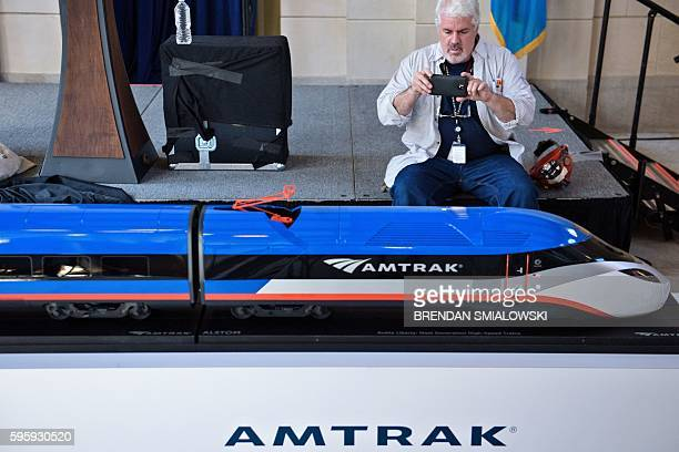 Worker takes a photo of a scale model of the next generation high speed Amtrak train after an unveiling event att Amtrak's Joseph R. Biden, Jr.,...