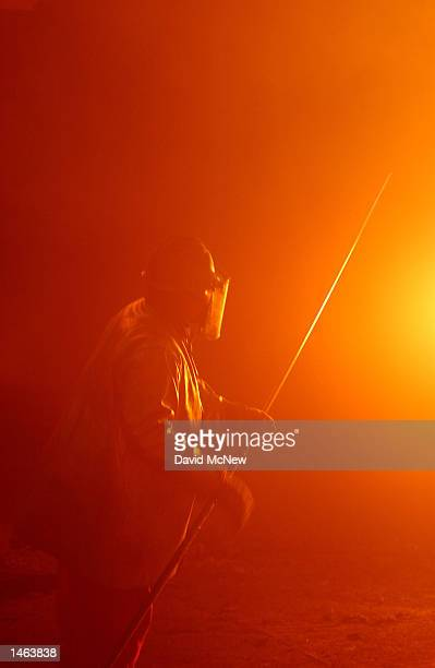 A worker takes a sample of molten steel from the furnace to test its chemical makeup and temperature at the TAMCO steel mini mill on October 4 2002...