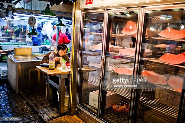 A worker takes a short break to eat some food as Tuna is seen refrigerated ready for sale at the Tsukiji fish market on February 28 2012 in Tokyo...