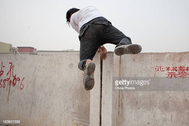 A worker takes a short cut going home by climbing a temporary wall around construction site of the Guangzhou Asian Games City to on June 16 2010 in...