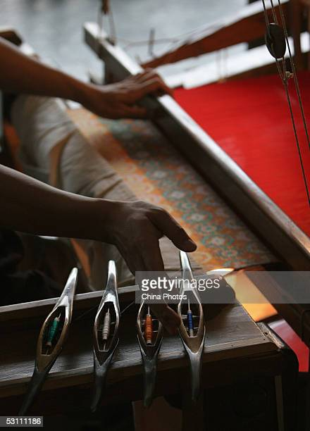 A worker takes a shuttle as he weaves Shu Brocade with an old traditional loom at a Shu Brocade factory on June 21 2005 in Chengdu of Sichuan...