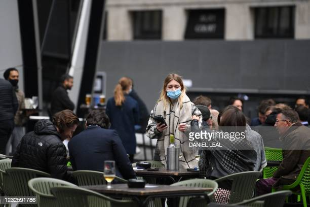 Worker takes customers' orders as they sit at tables outside a bar in the City of London on April 29, 2021. - Britain has been the European country...