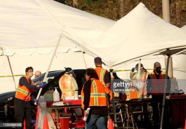 Worker takes down a tent in fear it might blow away due to high winds at a large scale COVID-19 vaccine site at California State University...