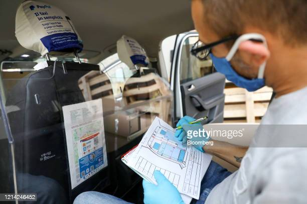 A worker takes measurement as he installs a plexiglass barrier inside a taxi at Plexismart Srl in Guidonia close to Rome Italy on Wednesday May 20...