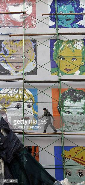 A worker takes off a covering from a mosaic panel made on a gable end of an apartment house in central Kiev on March 24 2010 during an artprotest...