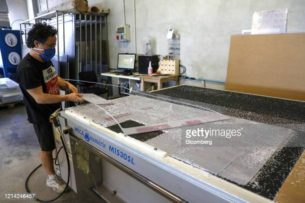 A worker takes off a plexiglass screen from the cutter at Plexismart Srl in Guidonia close to Rome Italy on Wednesday May 20 2020 Floortoceiling...