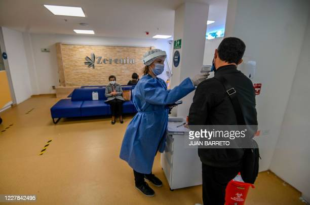 Worker takes the temperature of a patient as a meassure to prevent the spread of the COVID-19 coronavirus, at the entrance of the first Cannabis...