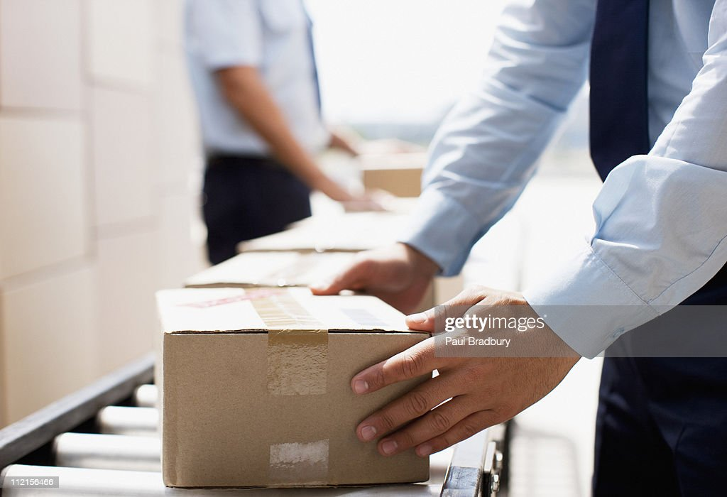 Worker taking box from conveyor belt in shipping area : Stock Photo