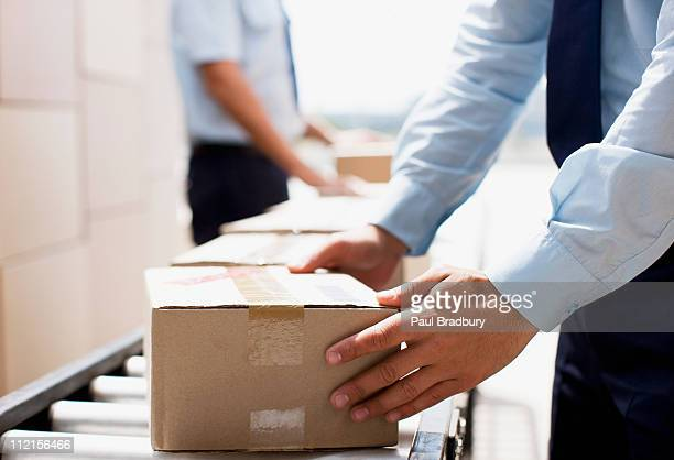 worker taking box from conveyor belt in shipping area - postal worker stock pictures, royalty-free photos & images