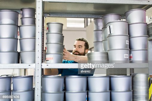 Arbeiter unter Tinte Dosen aus Regal an Druckmaschine