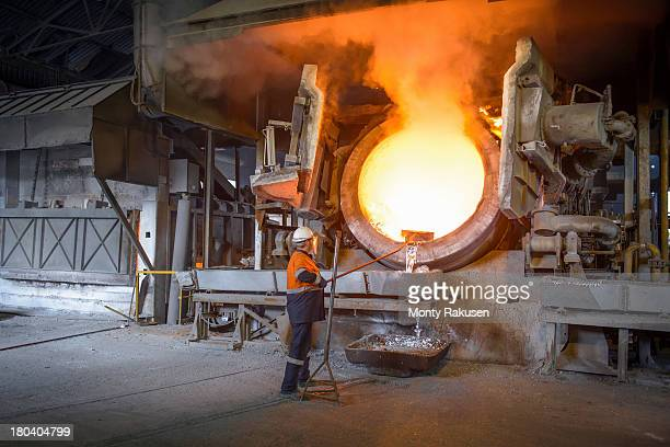 Worker taking sample from furnace in aluminium recycling plant