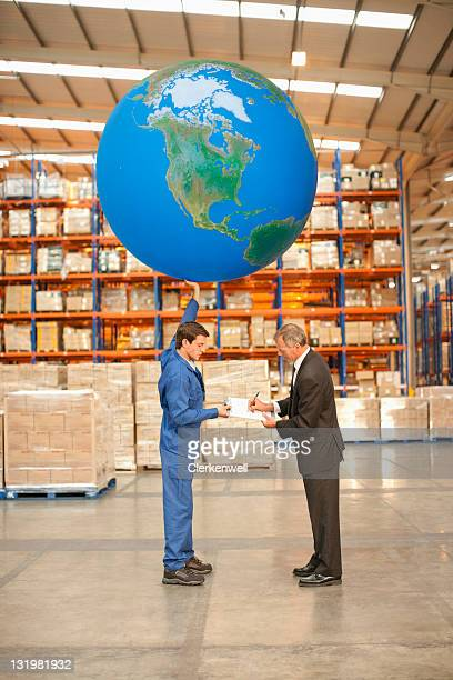 worker taking sign on paper with huge ball in other hand - man with big balls stock photos and pictures