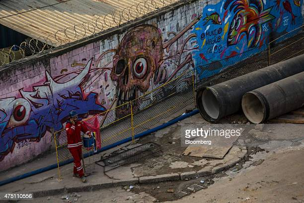 A worker talks on a mobile phone during a break at a construction site near the port in Rio de Janeiro Brazil on Thursday May 28 2015 Budget cuts...