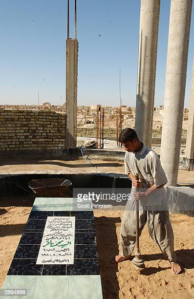 A worker tamps dirt at the grave of Grand Ayatollah Mohamed Bakr alSadr a revered antiregime cleric killed in 1980 by the Saddam Hussein regime on...