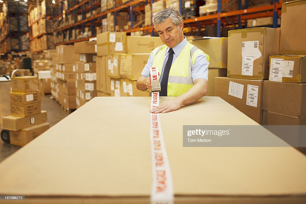 Worker taping box in warehouse : Stock Photo