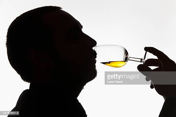 Worker tasting whisky in distillery