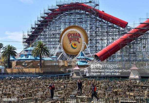 Worker tend to part of the World of Color water show as progress is made at Pixar Pier inside Disney California Adventure Park in Anaheim on Tuesday...