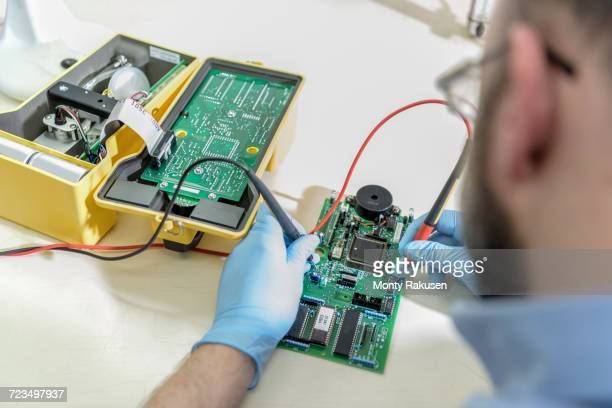 worker testing electrical components in laboratory - monty rakusen stock pictures, royalty-free photos & images