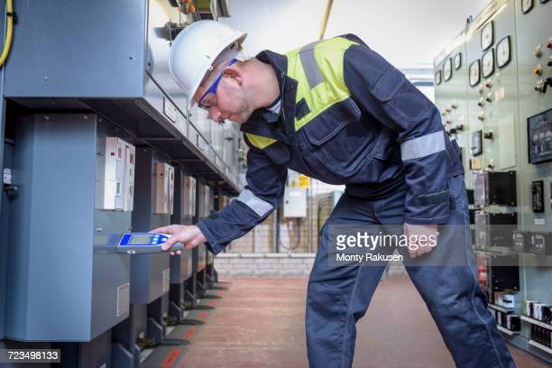 Worker testing for noise in electricity substation