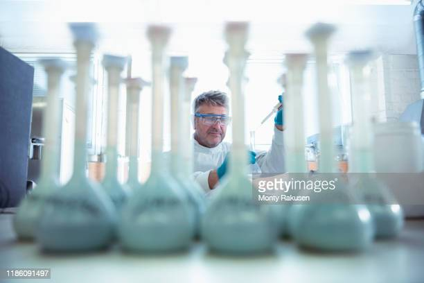 worker testing samples of titanium in titanium recycling plant - green coat stock pictures, royalty-free photos & images