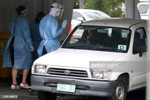 Worker tests a local resident at a COVID drive through testing clinic on January 08, 2021 in Brisbane, Australia. Brisbane will enter a three-day...