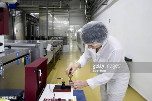 A worker tests a sample of freshly made chocolate at the Trostyanets confectionery plant operated by Mondelez International Inc in Trostyanets...