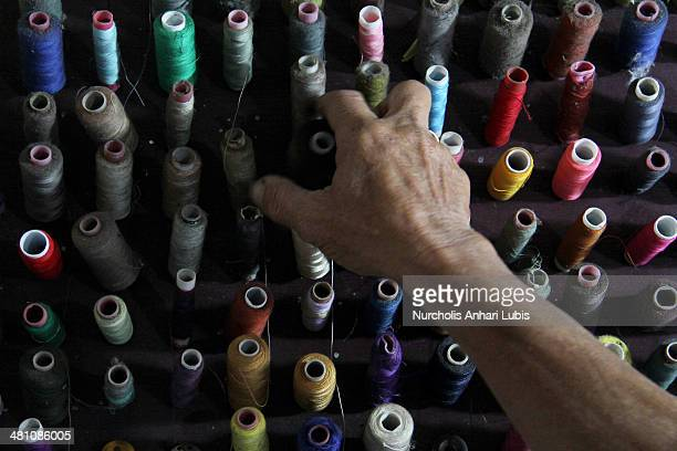 A worker thread takes material to design pets clothes workshop Doggy Boutique on March 28 2014 in Cimahi Bandung Java Indonesia Pets clothing in a...