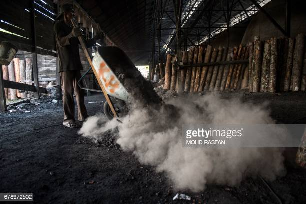 A worker throws ashes from a charcoal kiln in a traditional mangrove charcoal factory in Kuala Sepetang a village in Malaysia's central state of...