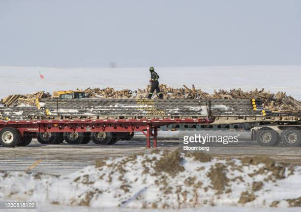 Worker ties down a load on a truck in a pipe yard for the Keystone XL pipeline in Oyen, Alberta, Canada, on Tuesday, Jan. 26, 2021. U.S. President...
