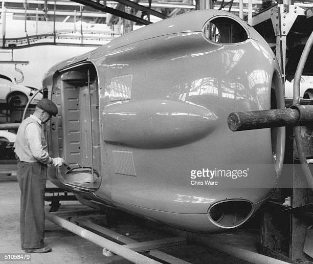 A worker touches up the paintwork on an EType Jaguar body shell at the company's Coventry works 25th May 1961
