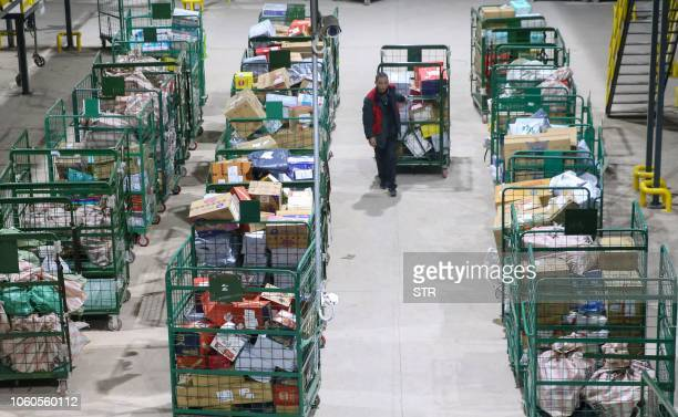 """Worker transfers packages after the """"Singles Day"""" shopping festival at a delivery company in Hengyang in China's central Hunan province early on..."""