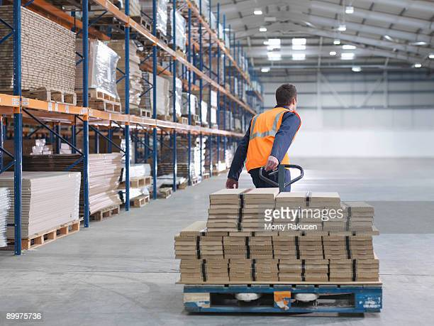worker transporting load in warehouse - monty rakusen stock pictures, royalty-free photos & images