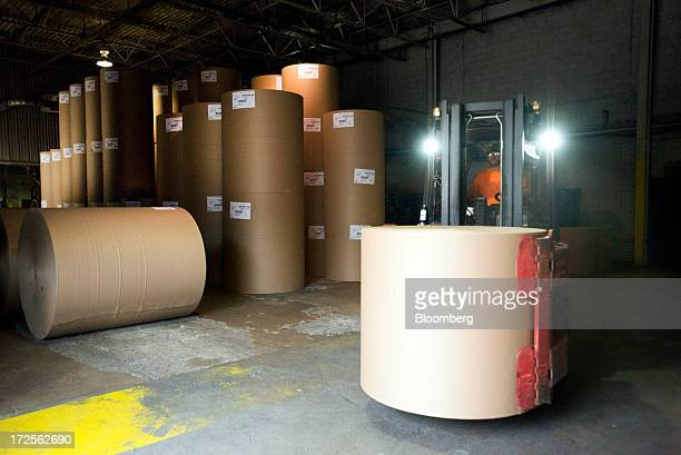 A worker transports a roll of new paperboard to the warehouse at Newark Recycled Paperboard Solutions in Baltimore Ohio US on Tuesday July 2 2013...