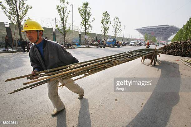 A worker transports bamboo for repairing peripheral residents' houses in front of the construction of the China Pavilion at the World Expo site on...