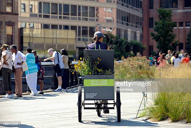 A worker transports flowers in a tricycle at the High Line park in New York US on Thursday Aug 16 2012 The High Line is a public park built on an...