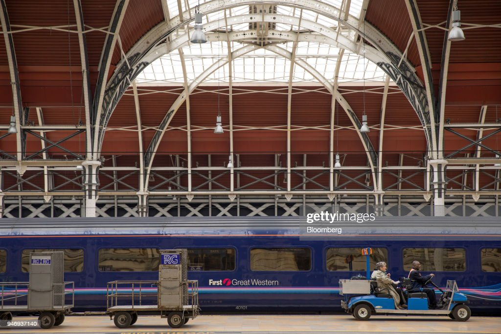A worker transports passengers on a motorized cart past a First Great Western train carriage, operated by FirstGroup Plc, at London Paddington railway station in London, U.K., on Monday, April 16, 2018. British train and bus operator FirstGroup Plc said it rejected an 'opportunistic' takeover proposal that private-equity firm Apollo Management made as the company struggles with under-performing rail routes in the U.K. and competition from discount airlines in the U.S. Photographer: Jason Alden/Bloomberg via Getty Images