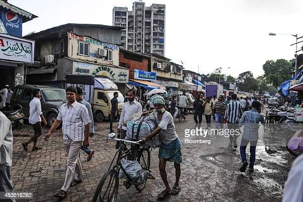 A worker transports sacks of goods on a bicycle in the Dharavi slum area of Mumbai India on Tuesday Aug 12 2014 Almost a year after Reserve Bank of...