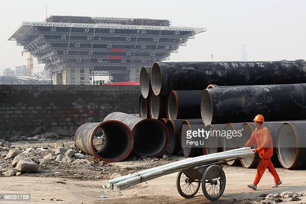 A worker transports the construction material in front of the construction for the China Pavilion at the World Expo site on April 21 2009 in Shanghai...