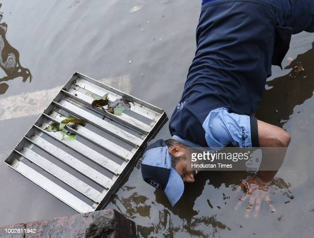 A worker tries to decongest a drain in front of Parliament House building during the third day of the Monsoon session of Parliament on July 20 2018...