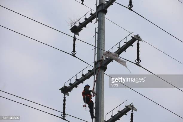 Worker tries to remove a piece of plastic from the high-voltage wire on February 14, 2017 in Xiangyang, Hubei Province of China. The technicians of...