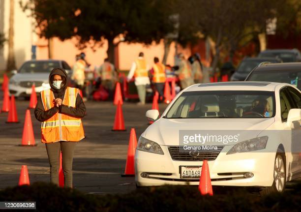 Worker tries to stay warm agains the cold wind next to a staging area for motorists who received the vaccine against COVID-19 to make sure there are...