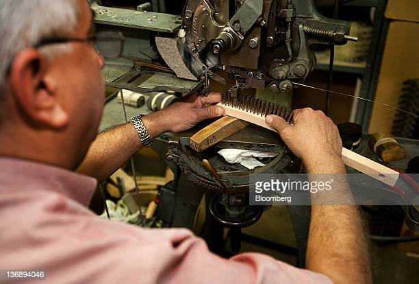 A worker trims stainless steel bristles at the Gordon Brush Manufacturing Co Inc production facility in Commerce California US on Tuesday Jan 10 2012...