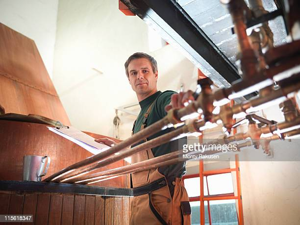 worker turning taps at copper in brewery - brewery stock pictures, royalty-free photos & images