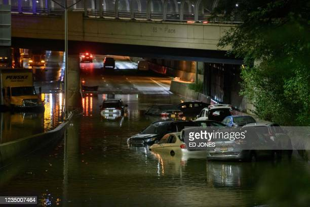 Worker unblocks drains on a street affected by floodwater in Brooklyn, New York early on September 2 as flash flooding and record-breaking rainfall...