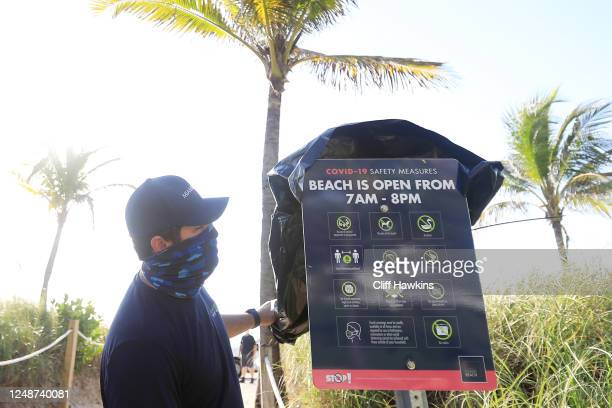 A worker uncovers a sign indicating the new beach COVID19 safety measures at an entrance to the beach on June 10 2020 in Miami Beach Florida...