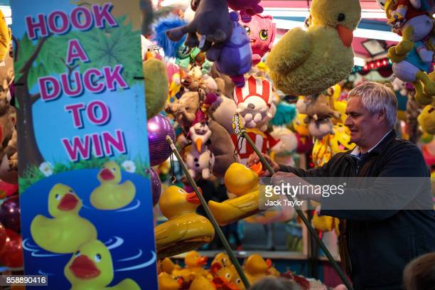 A worker unhooks a couple of plastic ducks at a fun fair game at the Nottingham Goose Fair in the Forest Recreation Ground on October 7 2017 in...